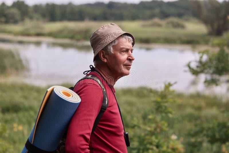 外形被射击有背包的和蓝色地毯、佩带的红色偶然毛线衣和盖帽,在河附近的enjoing的beautifulnature eldery人和 库存图片