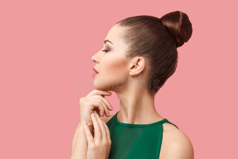 外形镇静严肃的美丽的年轻女人侧视图画象有小圆面包发型和构成的在与闭合的绿色礼服身分 库存图片