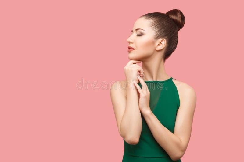 外形镇静严肃的美丽的年轻女人侧视图画象有小圆面包发型和构成的在与闭合的绿色礼服身分 免版税库存照片