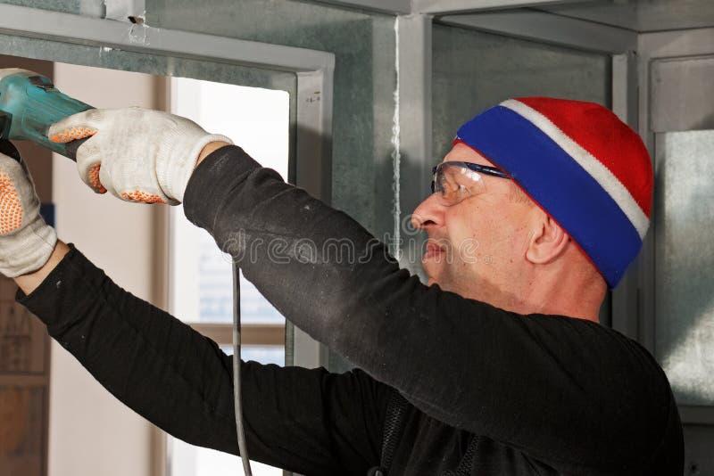 外来工人执行金属结构建筑和制造业  特写镜头画象,当完成工作时 库存图片