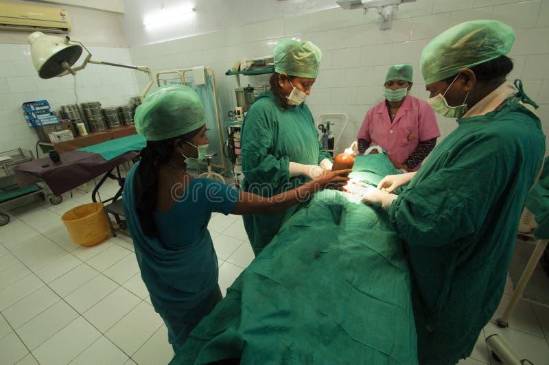外科医生和护士在比哈尔省,印度举办在一个少妇的输卵管结扎 免版税库存图片