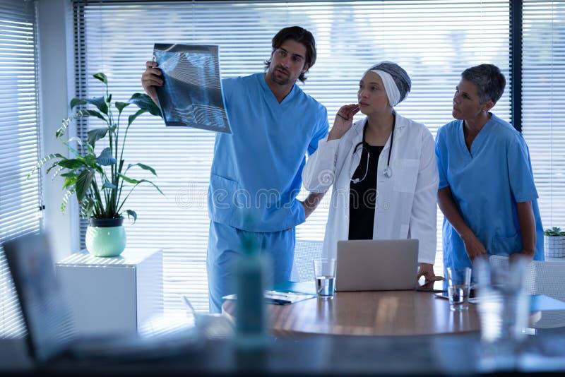 外科医生看和谈论在X-射线在诊所医院 库存图片