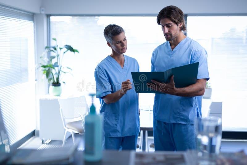 外科医生谈论在医疗文件在诊所在医院 图库摄影