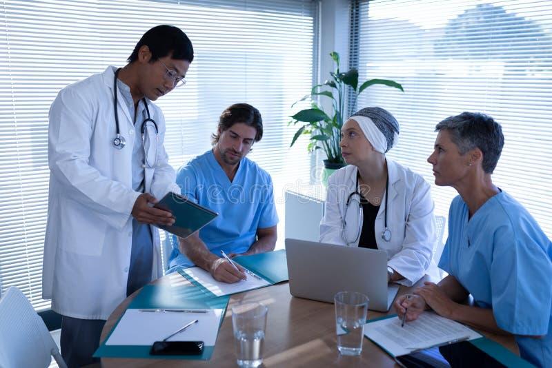 外科医生谈论在数字片剂在诊所在医院 免版税库存照片