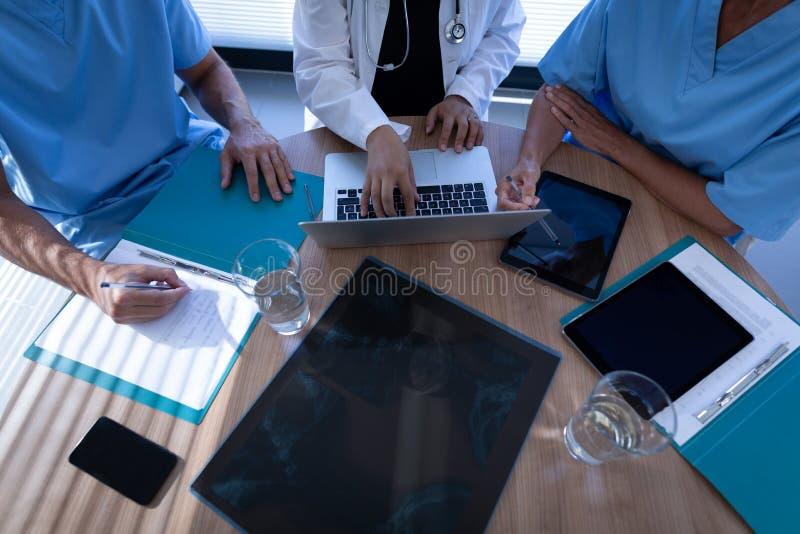 外科医生谈论在膝上型计算机在诊所在医院 图库摄影