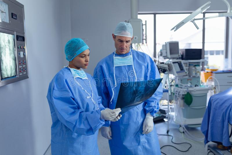 外科医生谈论在x光芒报告在手术室在医院 库存图片