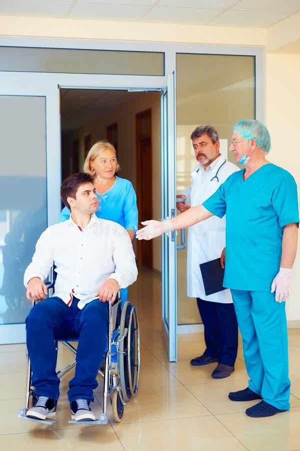 外科医生和医护人员谈话与轮椅的年轻成人人,在医院 免版税图库摄影