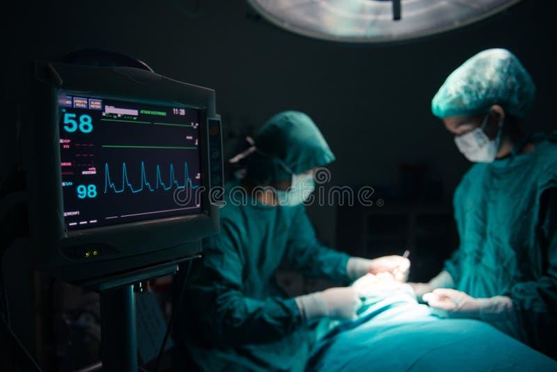 外科医生在外科手术室合作与患者一起使用监视  免版税库存图片