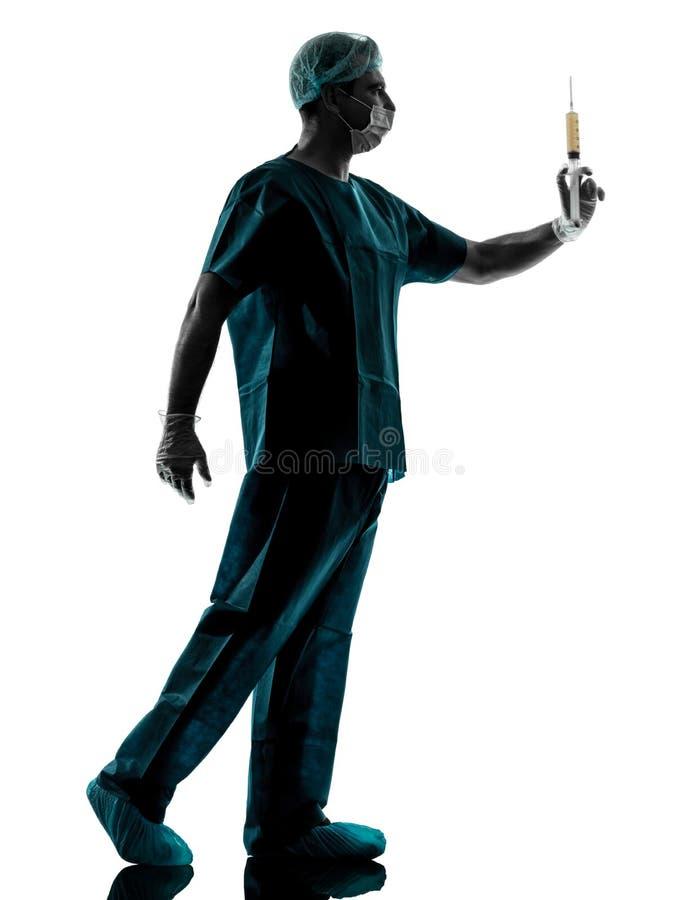 医治外科医生拿着手术针剪影的麻醉师人 免版税库存照片