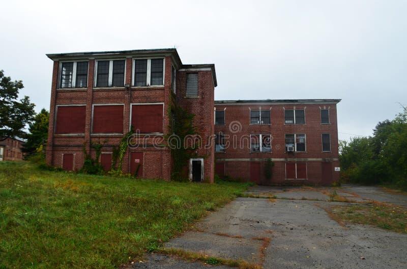 外部上和与残破的窗口的被放弃的砖收容所医院大厦 免版税库存照片
