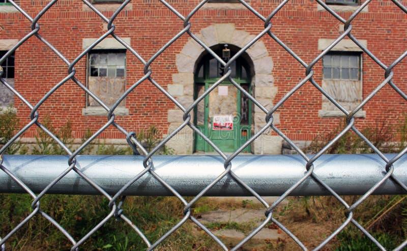 外部上和与链节篱芭围拢的残破的窗口的被放弃的砖收容所医院大厦 免版税图库摄影