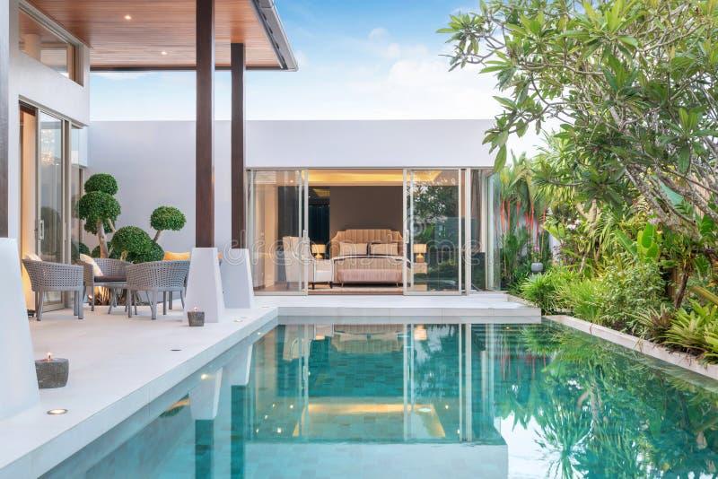 外部家或的房屋建设和显示与绿色庭院和卧室的室内设计热带水池别墅 免版税库存照片