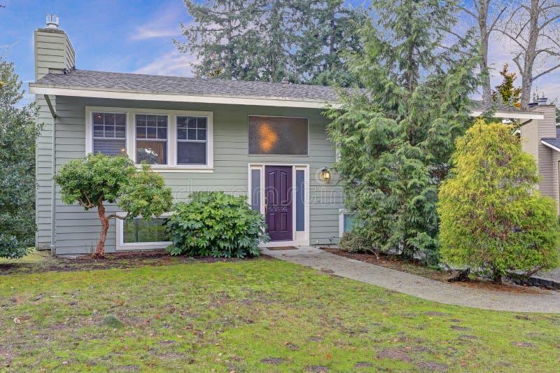 外部恰好更新在家与绿色房屋板壁和白色修剪 库存图片
