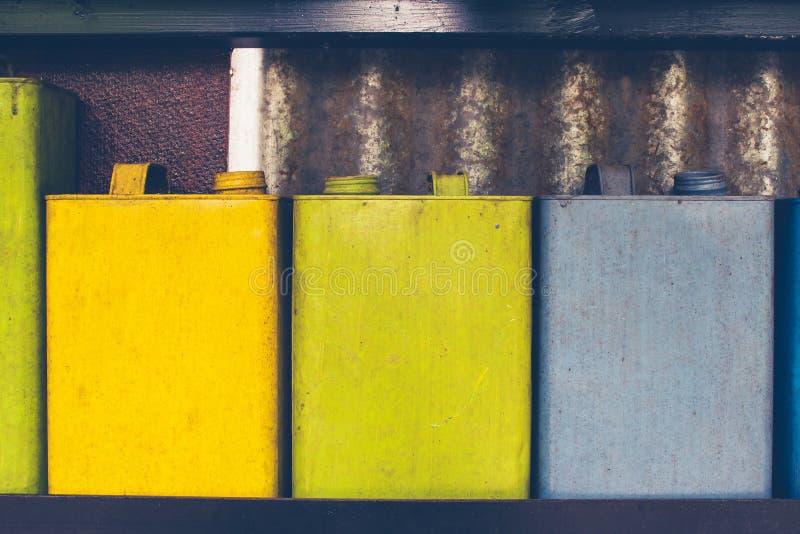 外部设计和装饰概念:五颜六色的使用的煤油容器或油行在墙壁上可能装饰 免版税库存照片