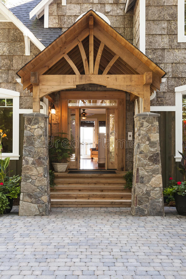 外部门廊和前门入口对美丽,高级乡间别墅有优质木头的和石头建筑材料 免版税库存照片