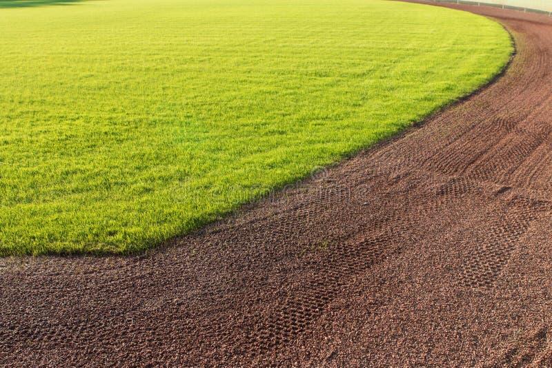 外野草和棒球场警告轨道土  库存照片