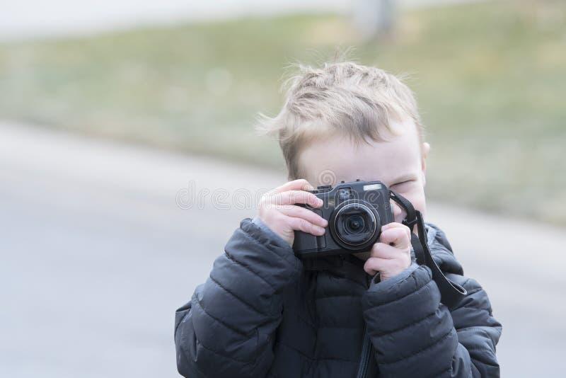 外面四岁的小孩男孩照相与照相机 免版税库存照片