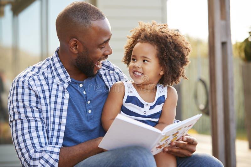 外面年轻黑父亲和女儿阅读书 免版税库存图片