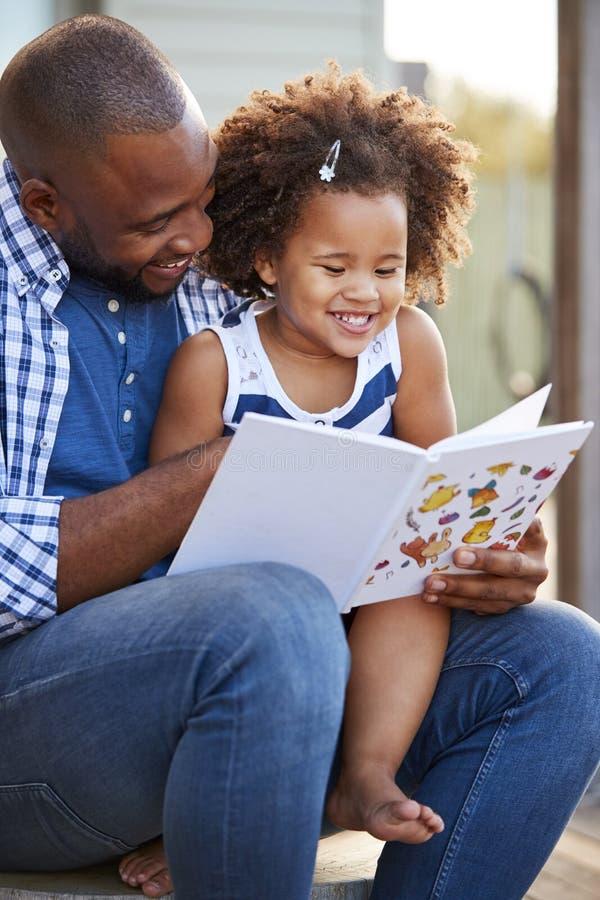 外面年轻黑父亲和女儿阅读书 免版税图库摄影