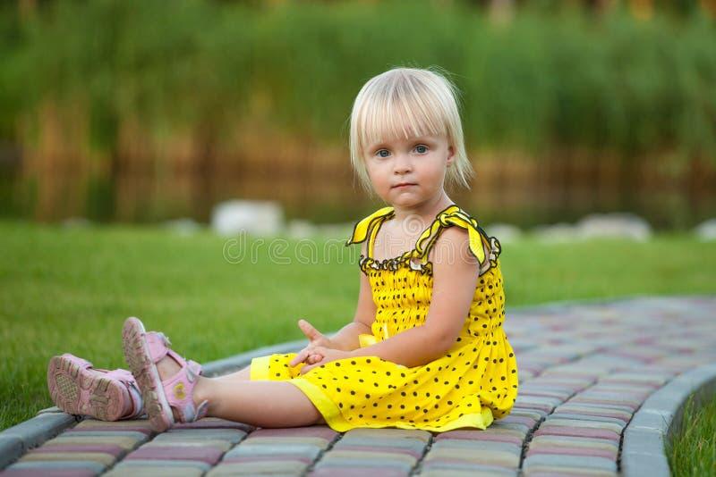 外面美丽的白肤金发的女孩 免版税库存图片