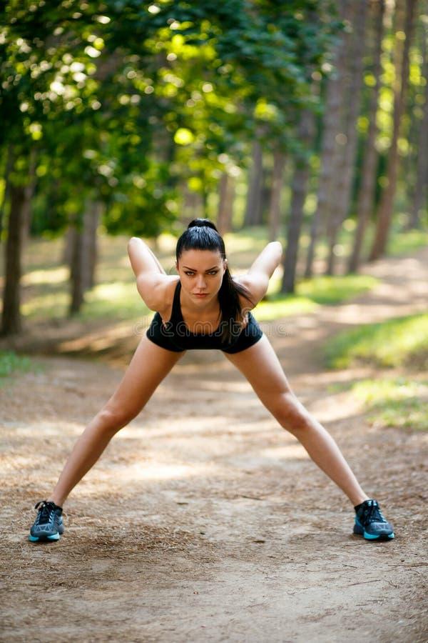 外面运动服锻炼的深色的亭亭玉立的年轻女人,做身体伸展运动在公园 免版税库存照片