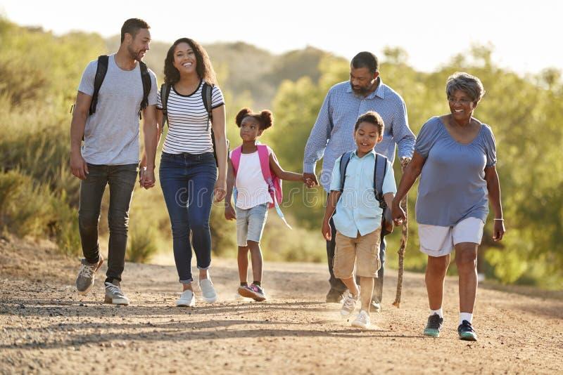 多一起远足在乡下的一代家庭佩带的背包 免版税库存图片