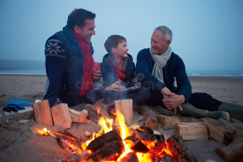 多一代家庭由火坐冬天海滩 图库摄影