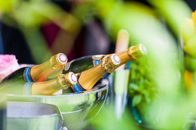多个瓶在银色碗的香槟在庭院里 库存图片