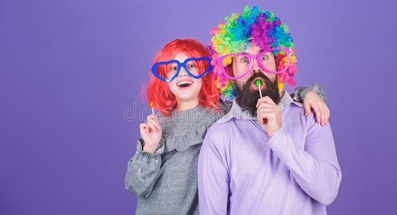 多么疯狂的是您的父亲 容易的单一方式是乐趣嬉戏的父母 人有胡子的父亲和女孩佩带五颜六色的假发一会儿 免版税库存照片