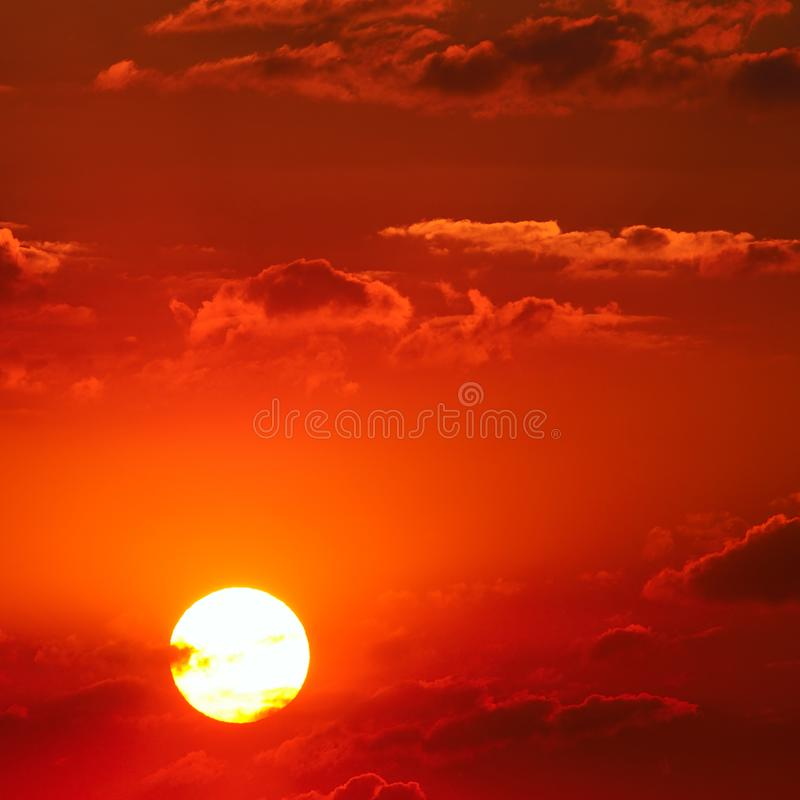 多云天空和明亮的太阳上升在天际 图库摄影