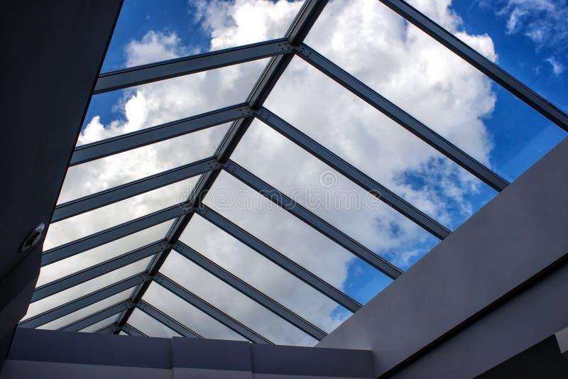 多云天空的看法通过玻璃屋顶 免版税库存图片