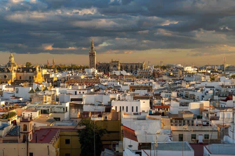 多云日落的塞维利亚历史街市包括大教堂,Plaza de EspaA±aa和其他 图库摄影