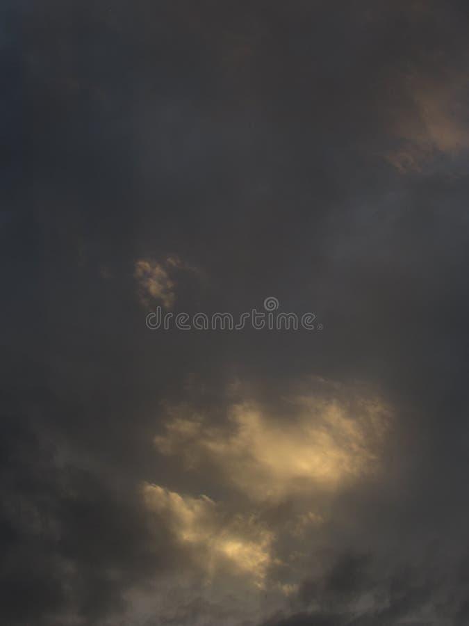 多云的灰色,与黑暗的剧烈的云彩的风雨如磐,黑暗的天空与在左边的明亮的黄色阳光 图库摄影