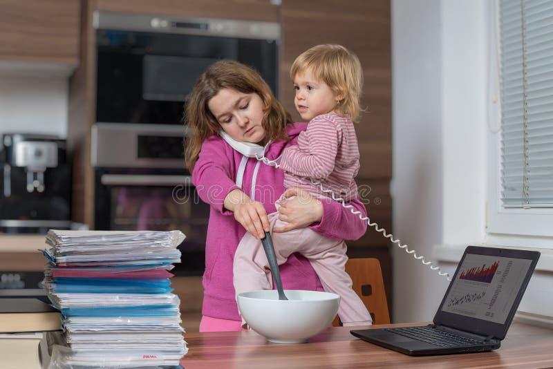 多任务母亲是在家看顾和工作 免版税图库摄影