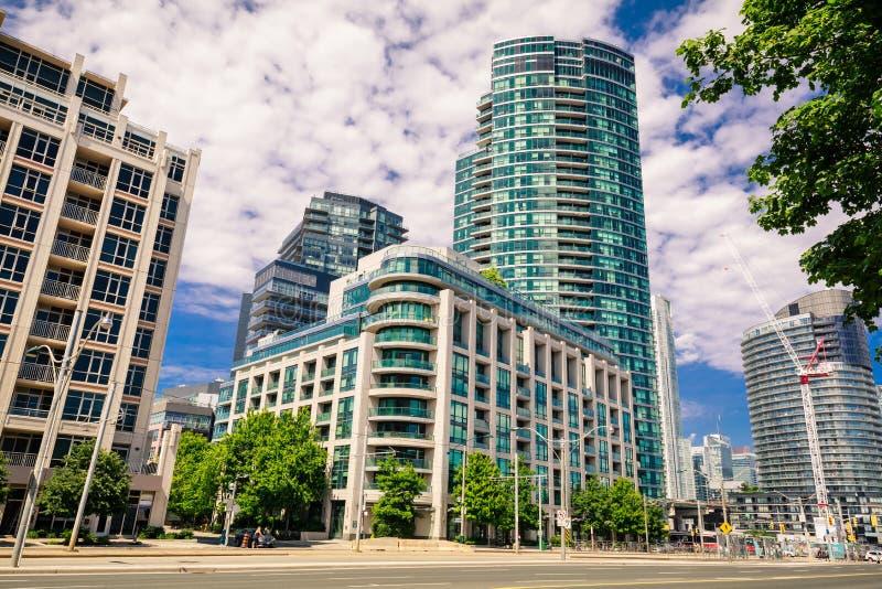 多伦多与现代时髦的住宅公寓房大厦的进城区域令人惊讶的,邀请的走在backg的看法,汽车和人们 免版税库存照片