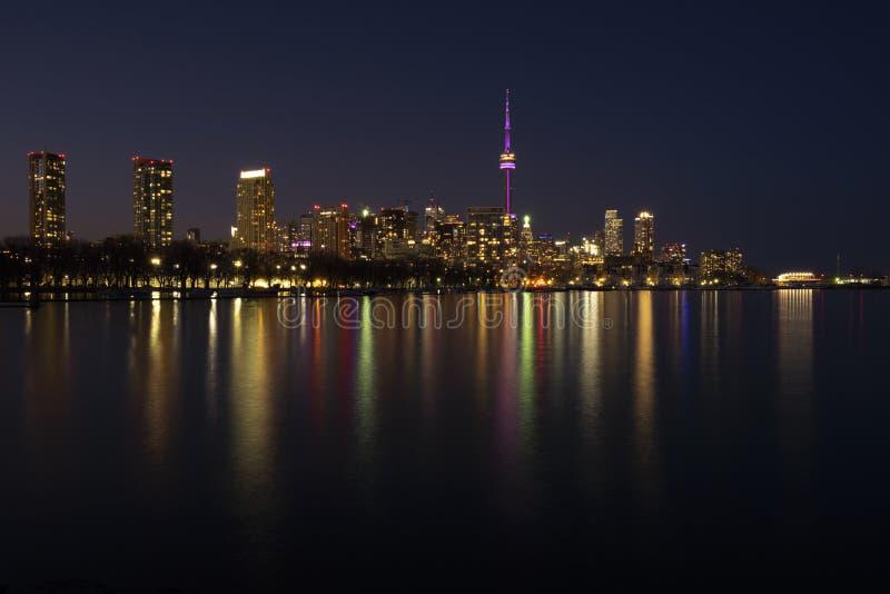 多伦多市地平线在晚上,清楚的黑暗的天空,在安大略湖镇静水表面的五颜六色的光反射  免版税库存照片