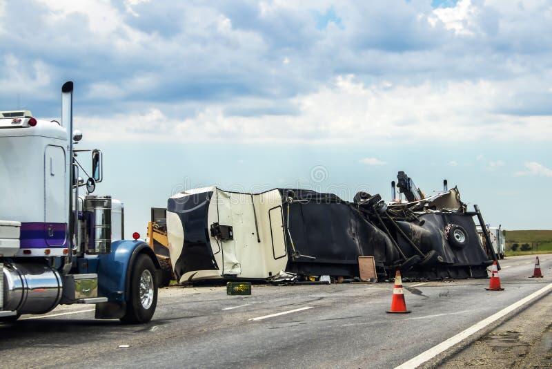 多余的事物或人RV在有设法妓女的卡车的高速公路翻转了得到它路,并且两半停放了附近和交通锥体 免版税图库摄影
