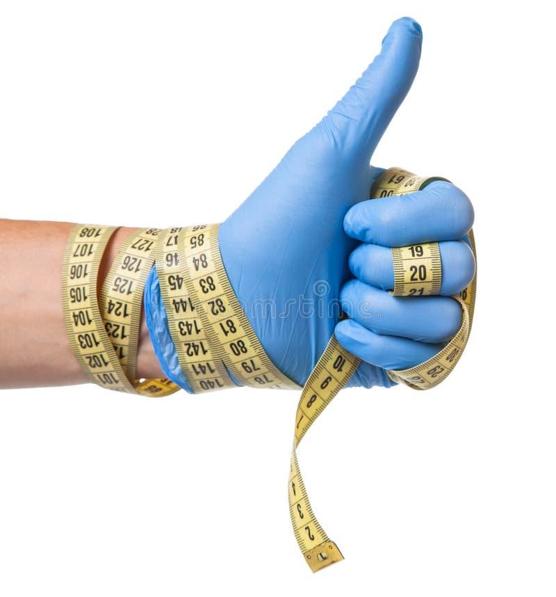 多余重量,减重,皮下脂肪切除术的概念 蓝色手套和测量的磁带的医生在他的手上在白色被隔绝 免版税库存图片