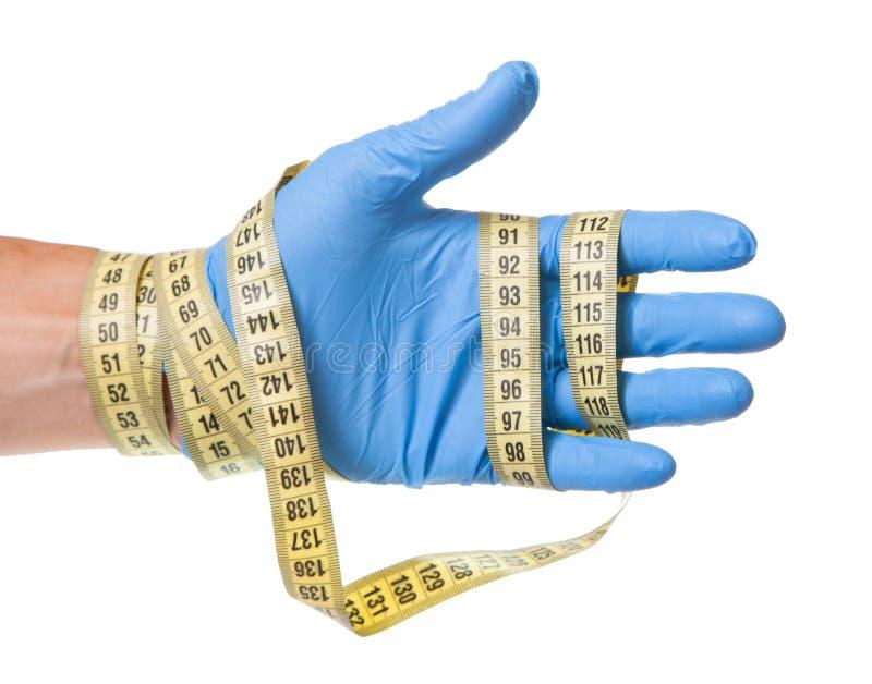 多余重量,减重,皮下脂肪切除术的概念 蓝色手套和测量的磁带的医生在他的手上在白色被隔绝 库存照片