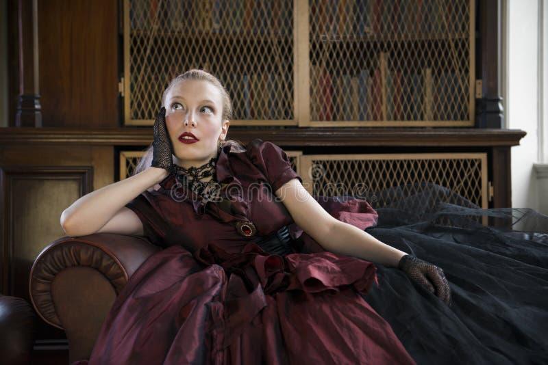 维多利亚女王时代的妇女在图书馆里 库存照片