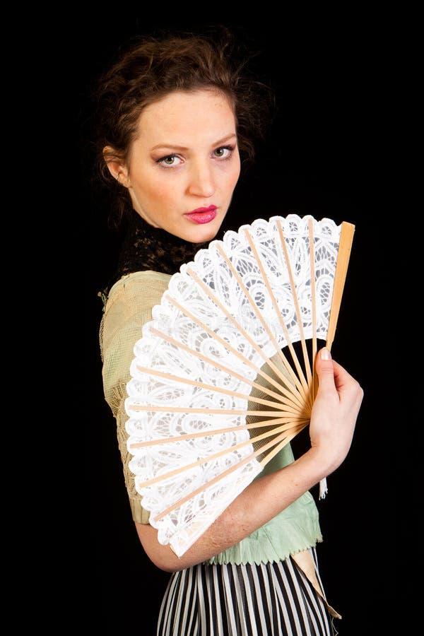 维多利亚女王时代的礼服的女孩有爱好者的在她的手上 免版税库存图片