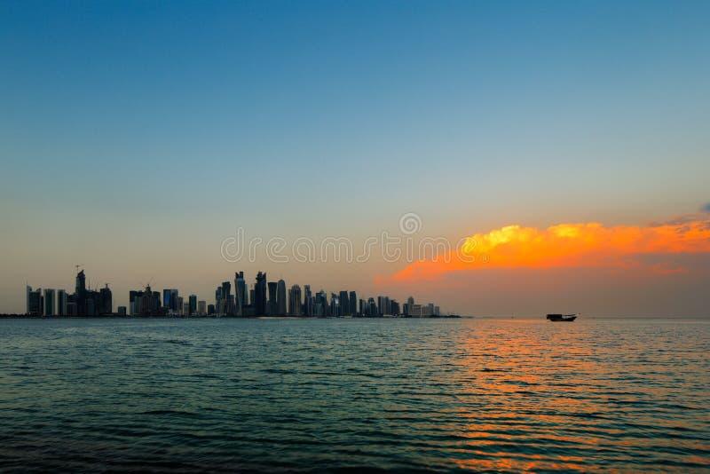 多哈,卡塔尔:在城市地平线的一朵美丽的日落云彩 库存图片