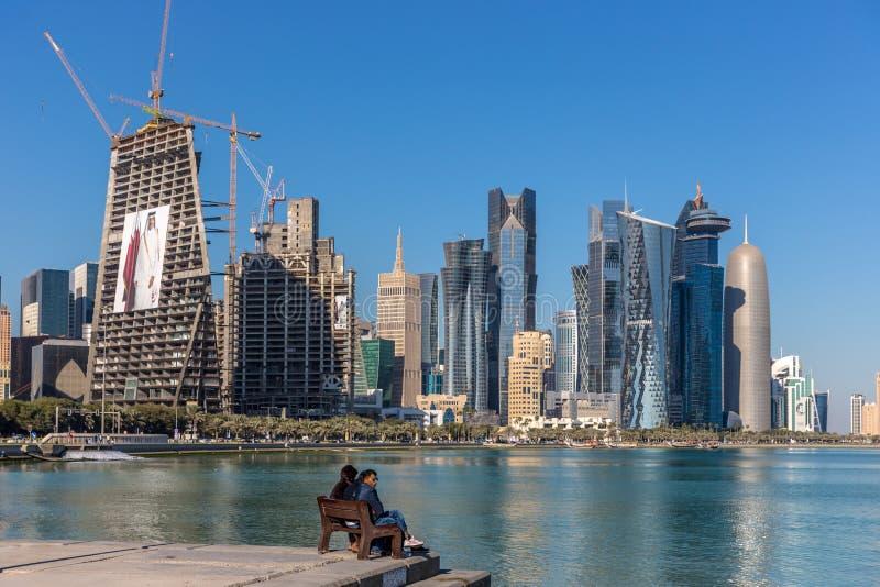 多哈,卡塔尔- 2018年1月8日-享受一美好的天的本机在多哈,大厦在背景,蓝天天中 免版税库存照片