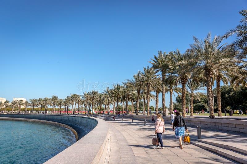 多哈,卡塔尔- 2018年1月9日-走接近与棕榈树树荫的海湾的游人在一蓝天天在多哈,卡塔尔的首都 库存图片