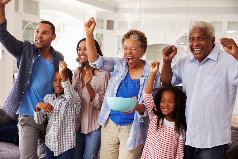 多在电视的一代黑色家庭观看的体育庆祝 免版税库存照片