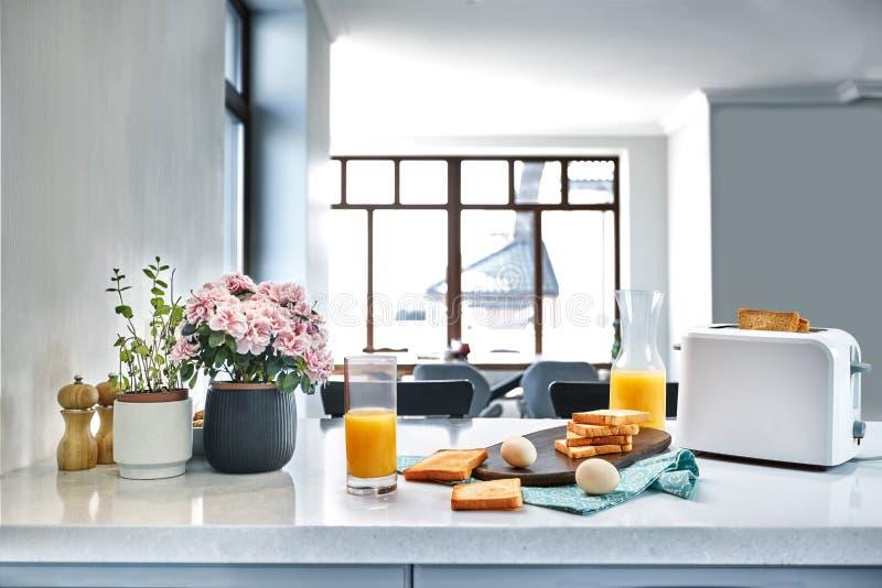 多士炉用新鲜的多士、鸡蛋和杯在轻的厨房用桌上的橙汁过去 免版税库存照片