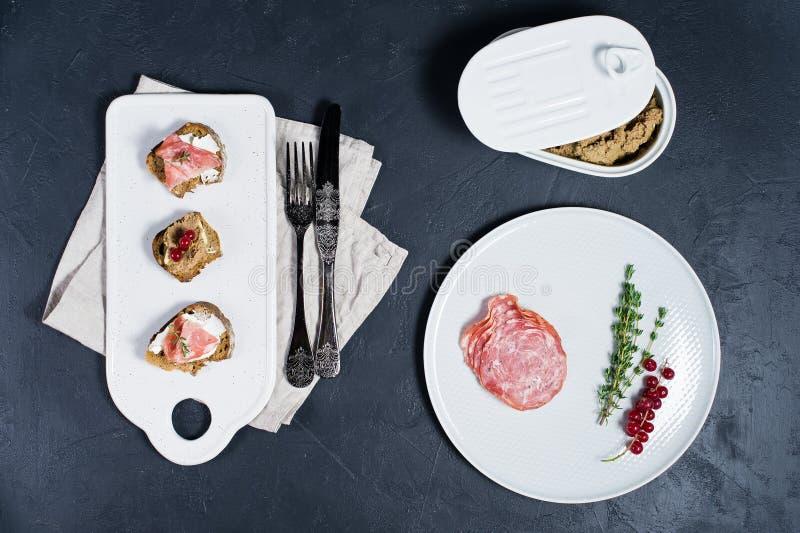 多士用在一块白色砧板的帕尔马、蒜味咸腊肠和鹅头脑 免版税库存图片