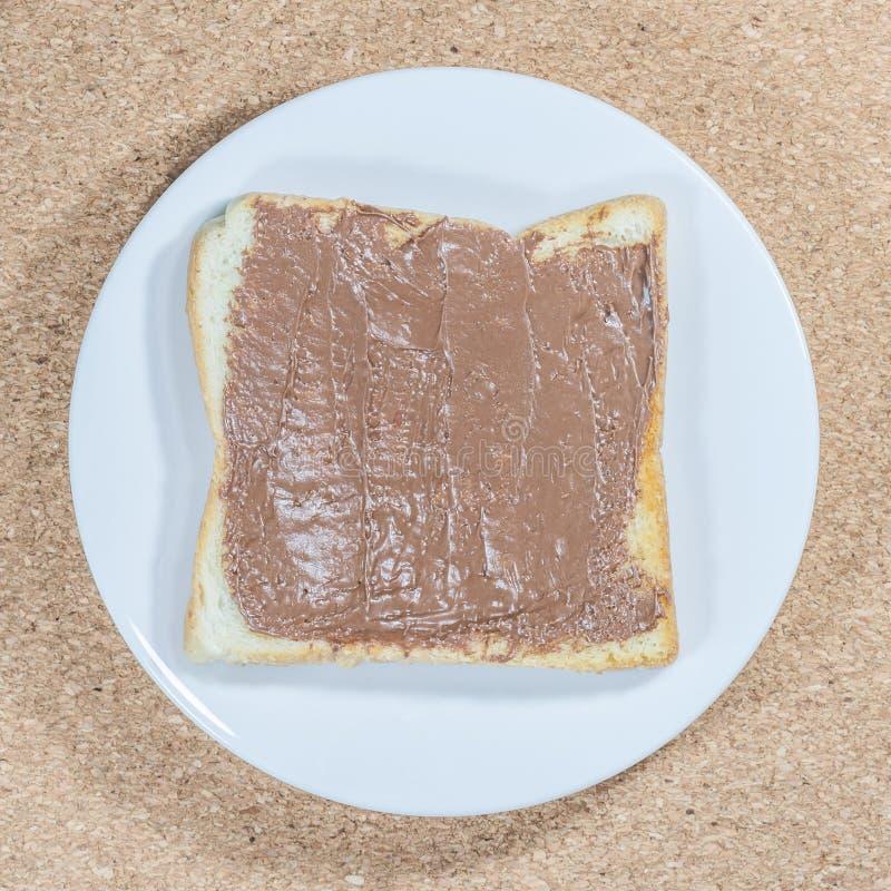 多士用巧克力在木板材backg的白色板材传播了 免版税库存图片