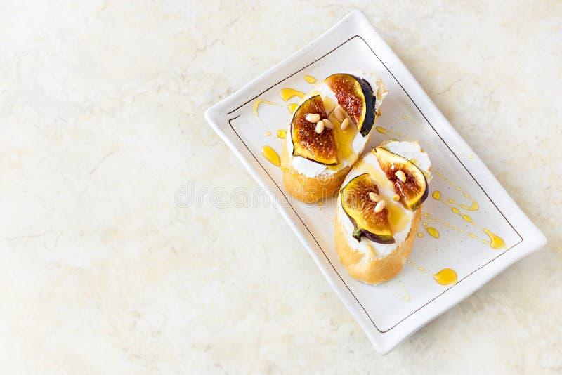 多士Bruschetta用无花果、山羊乳干酪和蜂蜜 白色backgrou 库存照片