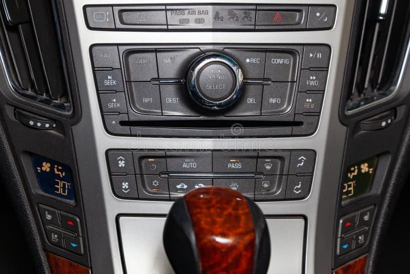 多媒体系统的控制板、收音机、电话、激昂的位子和透气、紧急刹车按钮和一个孔为 库存照片